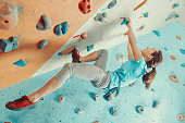 Sporty young woman training in a colorful climbing gym. Free climber girl climbing up indoor