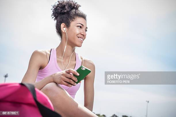 Young woman training, listening to earphones