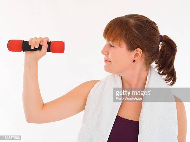 Young woman training with dumbbell