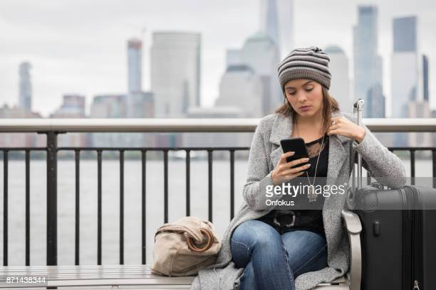 Young Woman Traveler Sitting on Bench Using Phone and Waiting with Suitcase