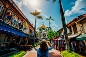 Young woman traveler traveling into The Masjid Sultan mosque located in Kampong Glam in Singapore city.