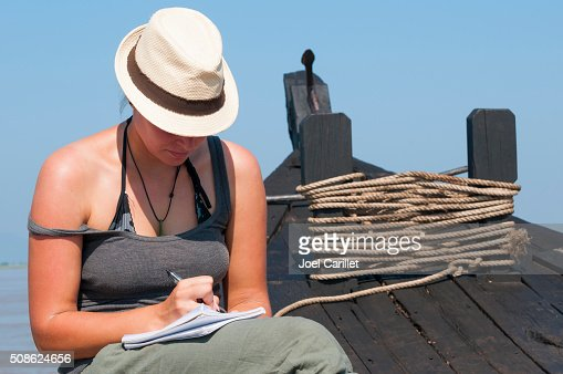 Young woman traveler writing in notebook : Stock Photo