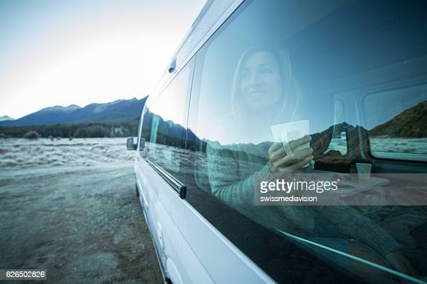 Young woman traveling in motor home looks through window
