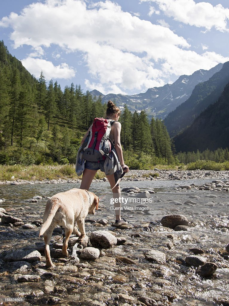 Young woman trekking with her dog