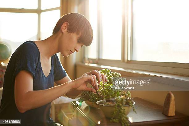 Young woman trimming her plants at home
