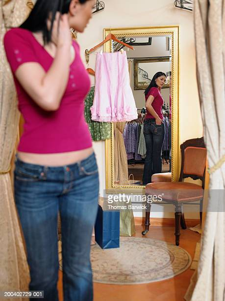 Young woman trying on clothing in dressing room, looking in mirror