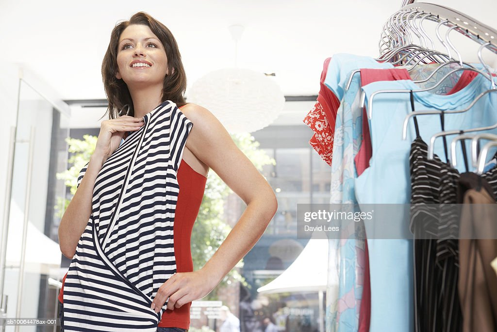 Young woman trying on dress in clothes shop, smiling : Stock Photo