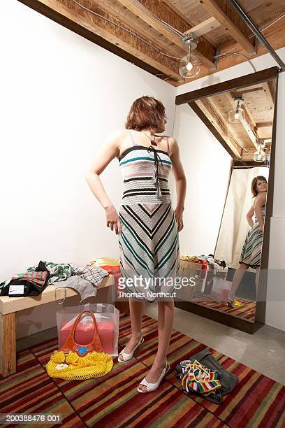 Young woman trying on dress in dressing room, looking over shoulder