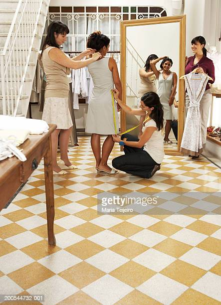 Young woman trying on dress in shop, three women assisting