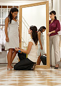 Young woman trying on dress in shop, two women assisting