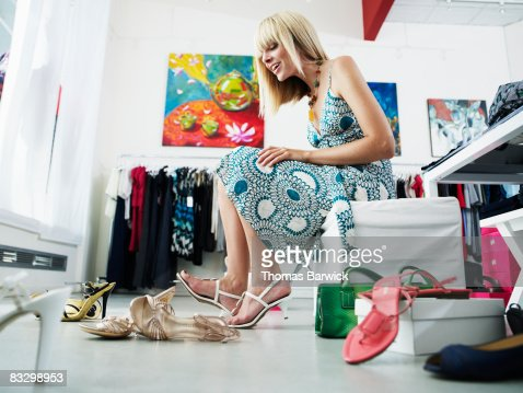 Young woman trying on shoes in clothing boutique : Stock Photo