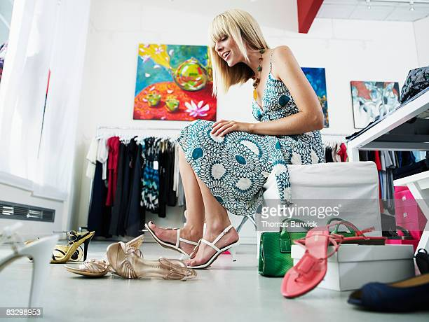 Young woman trying on shoes in clothing boutique
