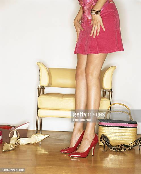 Young woman trying on shoes in shop, looking at feet, mid section