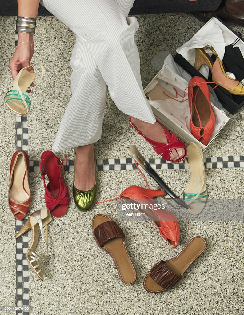 Young woman trying on shoes in shop, overhead view : Stock Photo