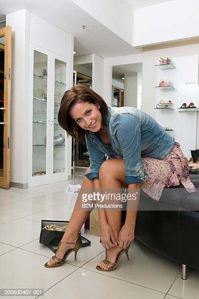 Young woman trying on shoes in shop, smiling, portrait