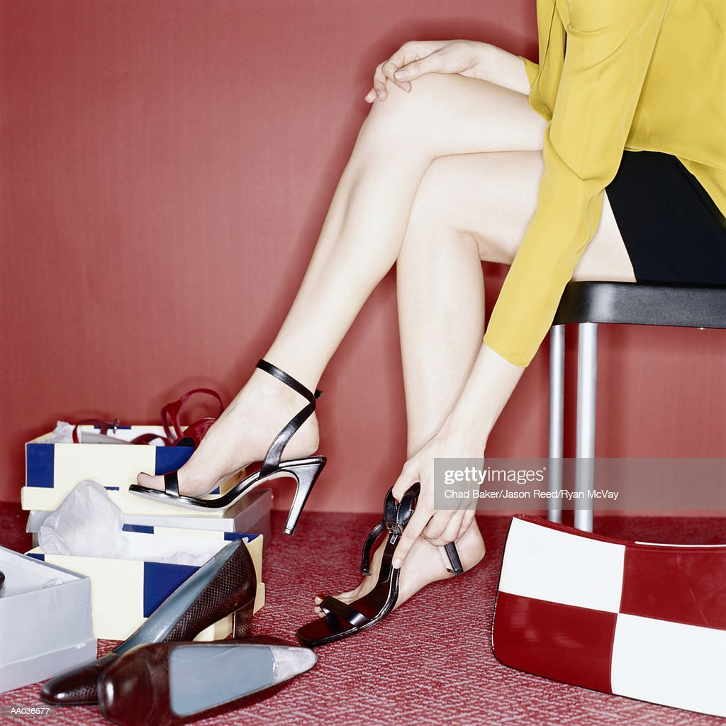 Young woman trying on shoes, low section, side view