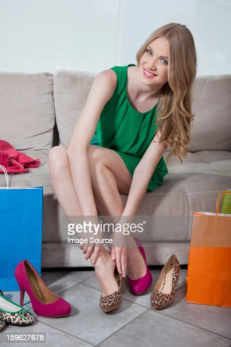 Young woman trying on shoes that she has bought : Stock Photo