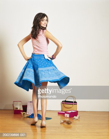 Young woman trying on skirt in shop, looking over shoulder, rear view : Stock Photo