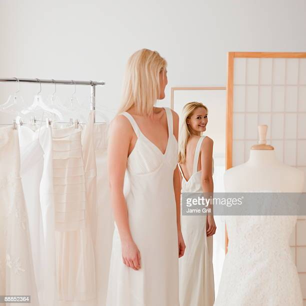 Young woman trying on wedding dress in bridal shop
