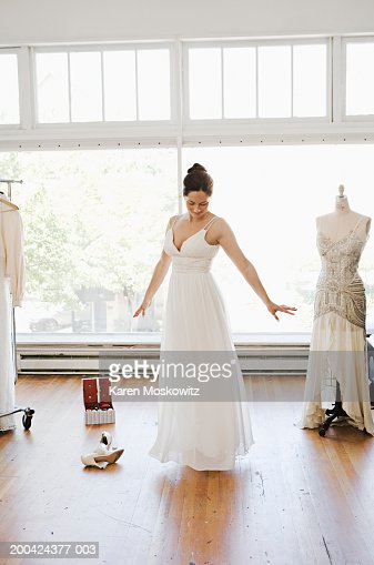 Young woman trying on wedding dress, looking down, arms outstretched : Stock Photo