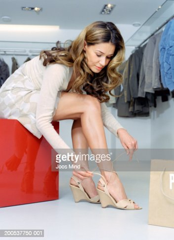 Young woman trying on wedge heel shoes in shop, low angle view