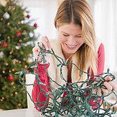 Young woman trying to untangle Christmas lights