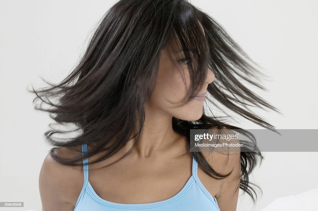 Young woman turning her head so that hair is in her face : Stock Photo