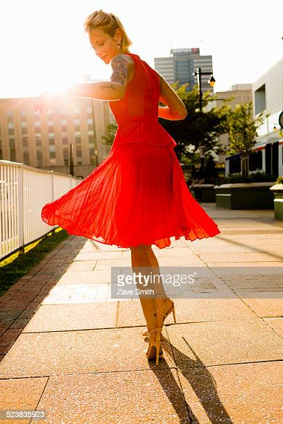 Young woman twirling whilst wearing red dress