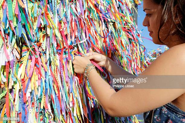 Young woman tying a fita (wish ribbon) outside Our Lady of Bonfim church