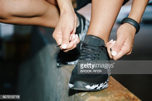 Young woman tying athletic shoelace