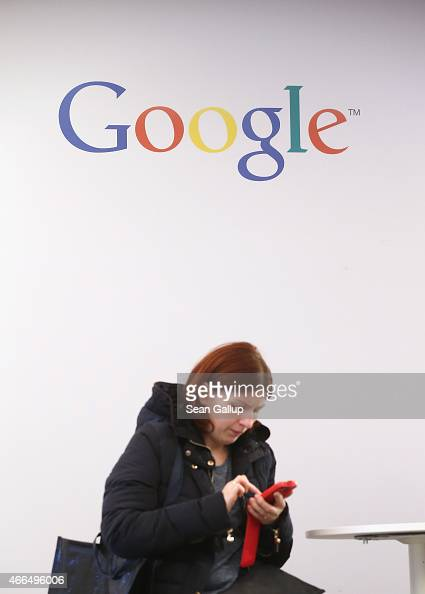 A young woman types on a smartphone under a Google sign at the 2015 CeBIT technology trade fair on March 16 2015 in Hanover Germany China is this...