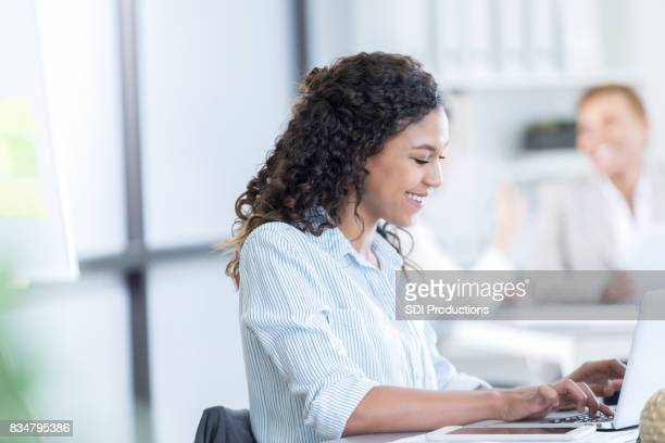 Young woman types on laptop at work