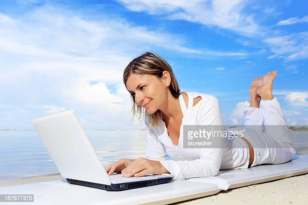 Young woman typing at laptop computer on a resort.