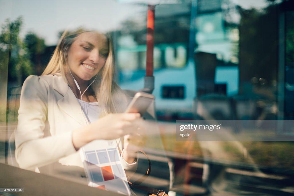 若い女性は彼女のスマートフォン入力にの公共交通機関です。 : ストックフォト