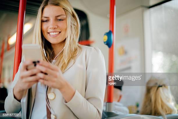 Junge Frau tippen auf ihrem Smartphone an die öffentlichen Verkehrsmittel.