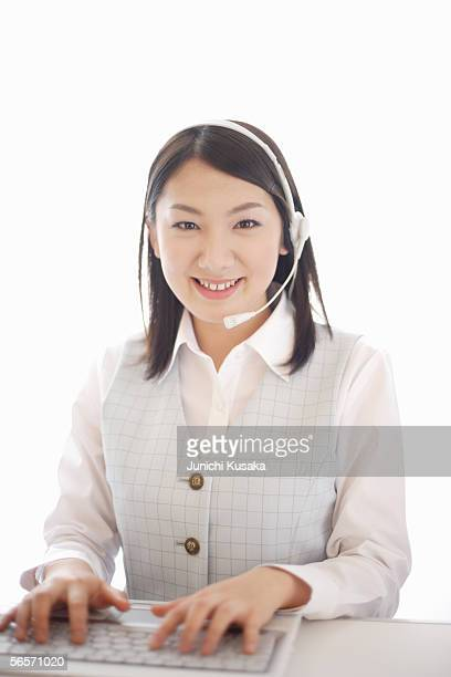 Young woman typing wearing headset