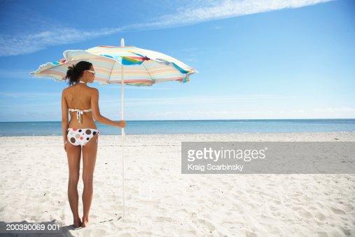 Young woman under beach umbrella, rear view