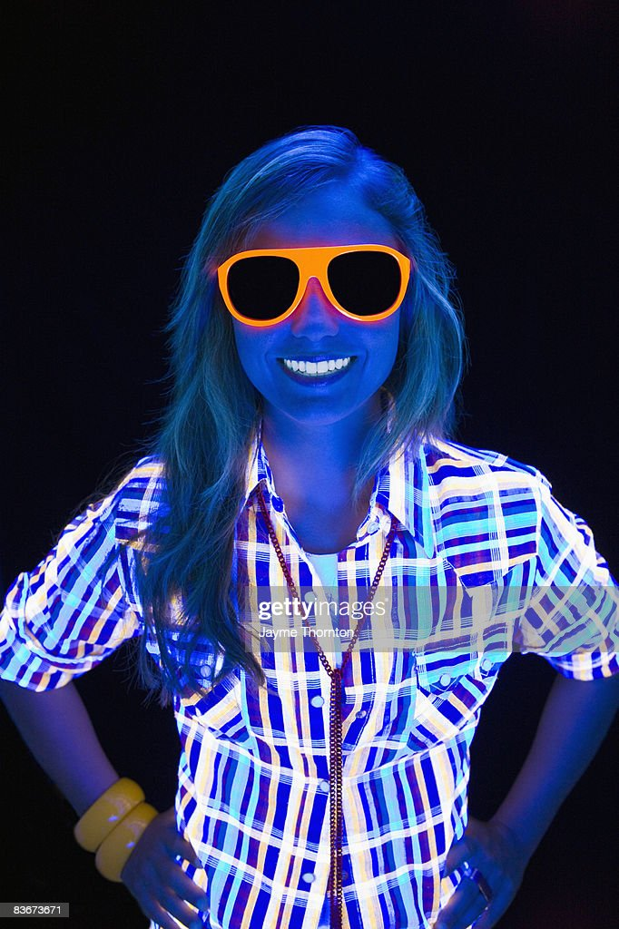 Young woman under black lights : Stock Photo