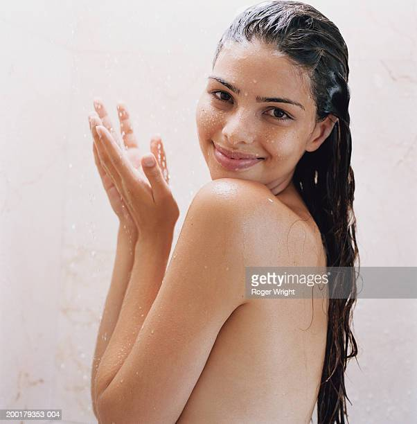 Young woman under shower, smiling, portrait
