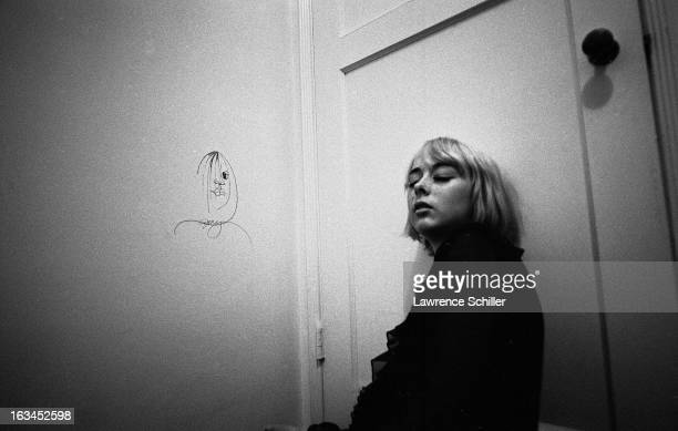 A young woman under the influence of LSD sits on the floor and leans eyes closed against door Los Angeles California 1966