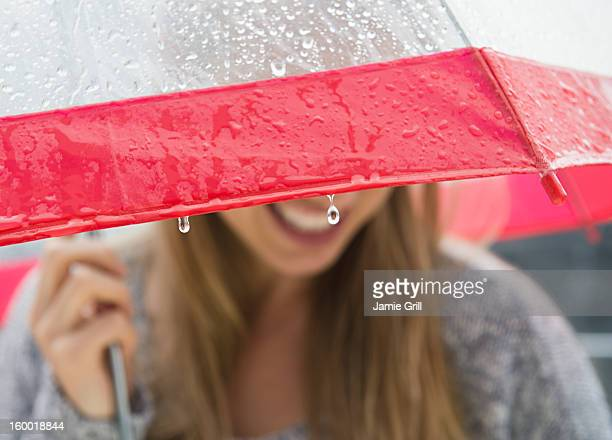 Young woman under umbrella in rain