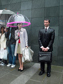Young woman under umbrella looking over at soaked businessman