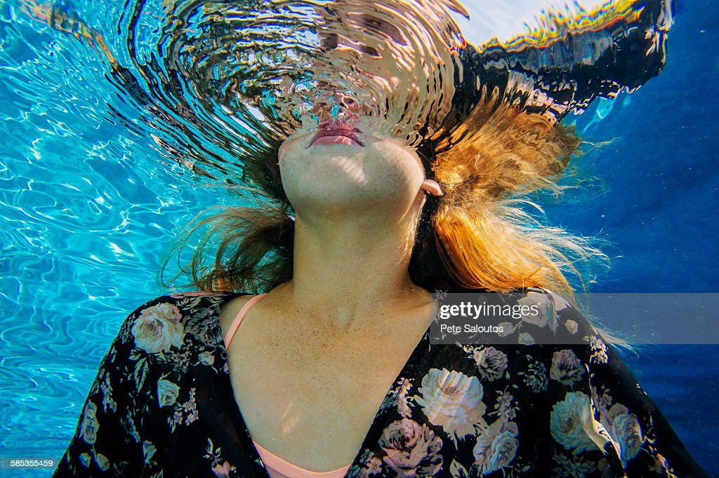 Young woman underwater, breaking through water surface