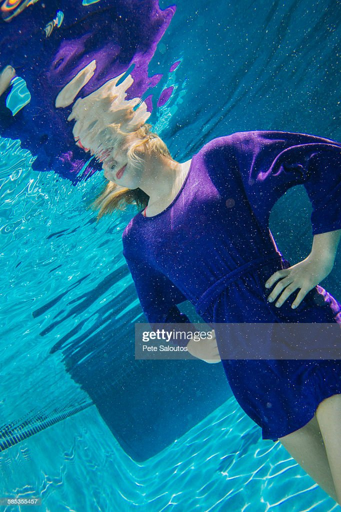Young woman underwater, hands on hips