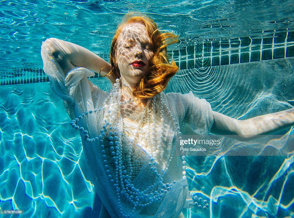 Young woman swimming underwater, wearing thin white shirt