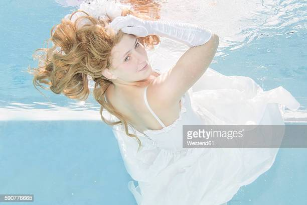Young woman underwater, wedding dress