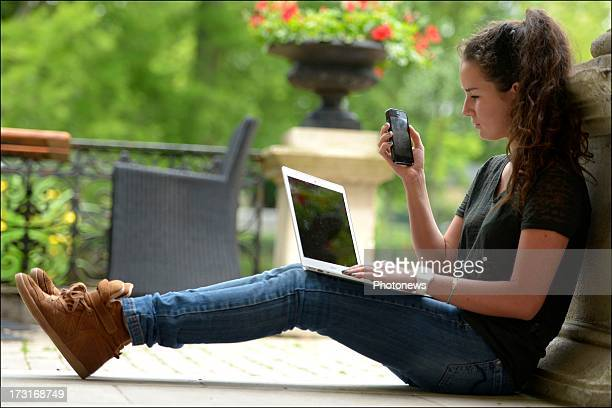 A young woman uses a mobile phone and laptop on June 25 2013 in Brussels Belgium