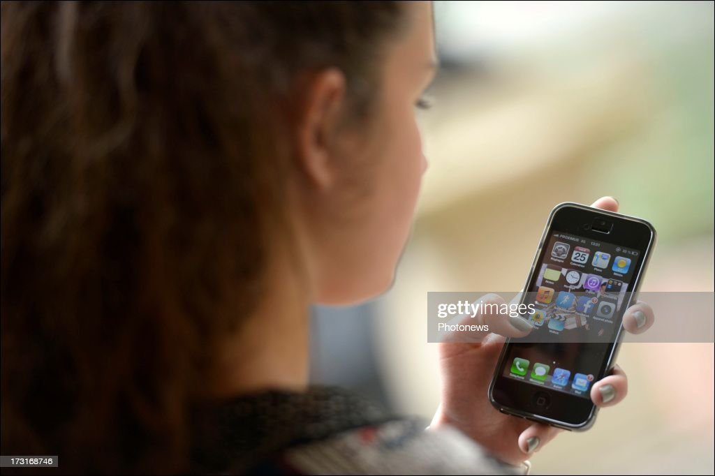 A young woman uses a mobile phone on June 25, 2013 in Brussels, Belgium.