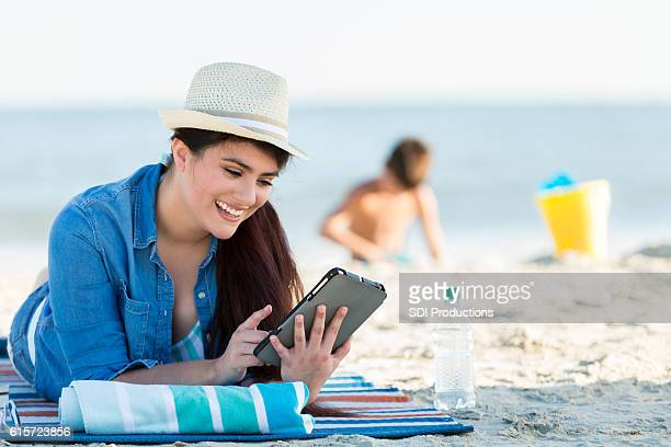 Young woman uses e-reader on the beach