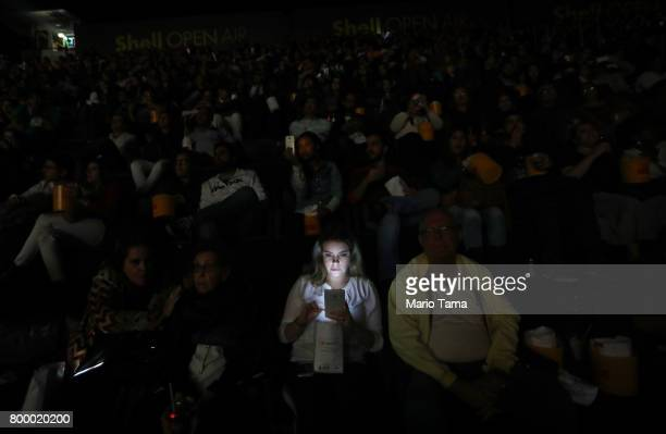 A young woman uses her cell phone during previews before the start of the James Bond film 'Skyfall'at the Shell Open Air cinema at Gloria Marina on...